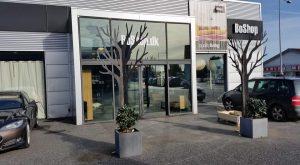 Træ i cortenstål foran butiksfacade